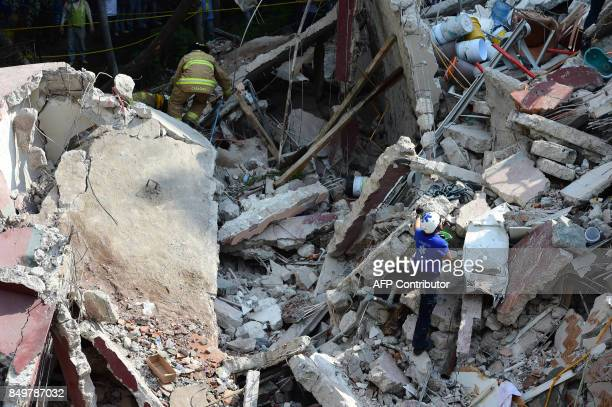 Rescuers firefighters policemen soldiers and volunteers remove rubble and debris from a flattened building in search of survivors after a powerful...