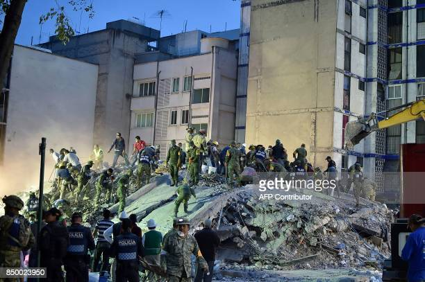Rescuers firefighters policemen soldiers and volunteers remove rubble and debris from a flattened building in search of survivors in Mexico City on...