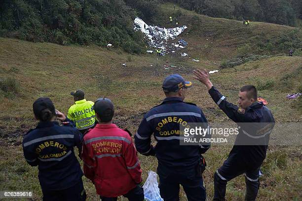 Rescuers gesture near the wreckage of the LAMIA airlines charter plane carrying members of the Chapecoense Real football team that crashed in the...