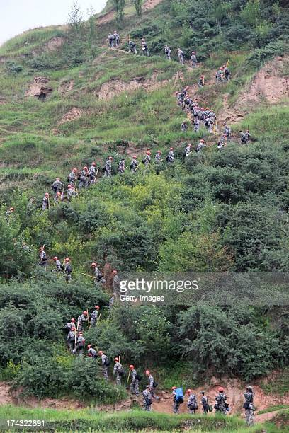 Rescuers head to the site of a mudslide at Tongxin village on July 23 2013 in Minxian China At least 95 people were killed and more than 1000 people...