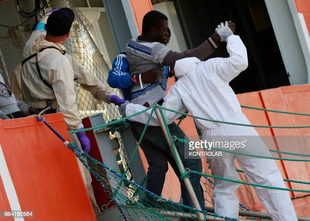 Rescuers help immigrants are disembarked in Salerno from rescue ship Siem Pilot after being saved in Mediterranean sea on May 26 2016