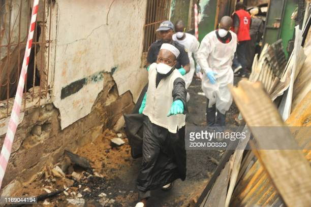 Rescuers hold a body after a fire at a Koranic school that killed at least 26 children and two teachers in Monrovia Liberia on September 18 2019...
