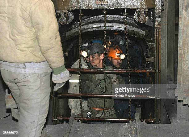 Rescuers in a lift prepare to rescue trapped miners out after a blast accident occured at Liuguantun Colliery in Kaiping District on December 7, 2005...