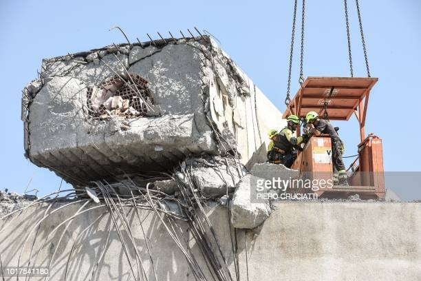 TOPSHOT Rescuersinspect the rubble and wreckages at the Morandi motorway bridge two days after a section collapsed in Genoa on August 16 2018 A vast...