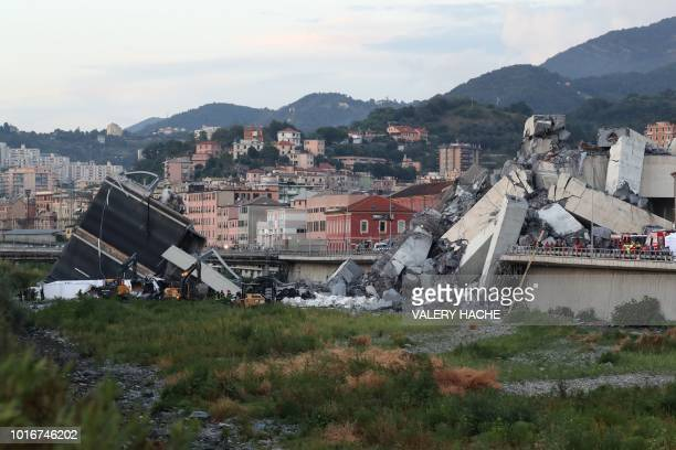 TOPSHOT Rescuers inspect the rubble and wreckages by the Morandi motorway bridge after a section collapsed earlier in Genoa on August 14 2018 About...