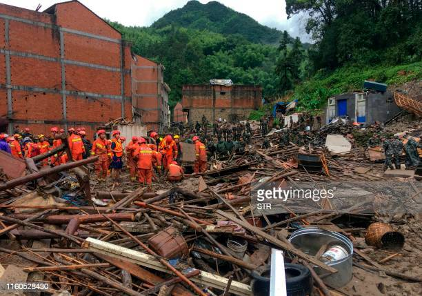 Rescuers look for survivors in the rubble of damaged buildings after a landslide caused by torrential rain from Typhoon Lekima at Yongjia in Wenzhou...
