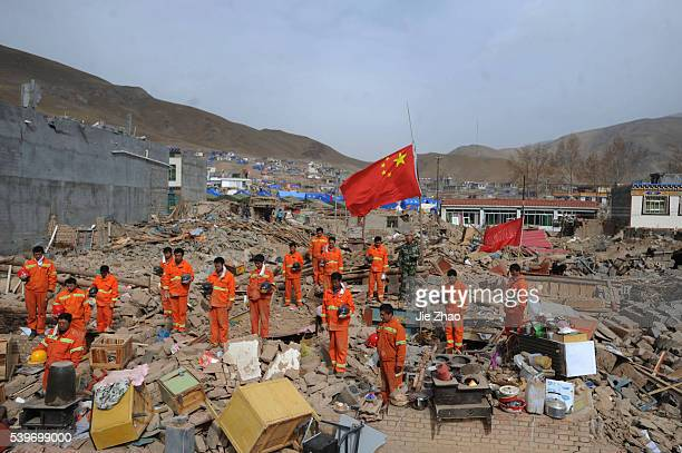 Rescuers mourn on the debris of collapsed buildings while the Chinese national flag is flown at half-mast in the earthquake-hit Gyegu town of Yushu...