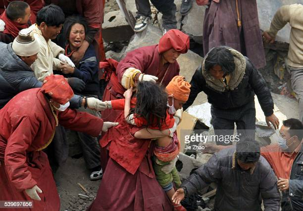 Rescuers move a 13-year old girl out from debris of destroyed house with her mother in the earthquake-hit town of Gyegu in Yushu County,Qinghai...