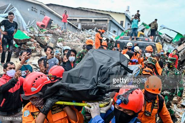 Rescuers move the body of a victim that was trapped in a collapsed building in Mamuju on January 16 a day after a 6.2-magnitude earthquake rocked...