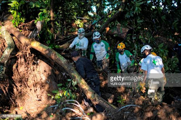 Rescuers of the Green Cross and a policeman work to remove rubble while searching for victims of a landslide in Nejapa, El Salvador on October 30,...