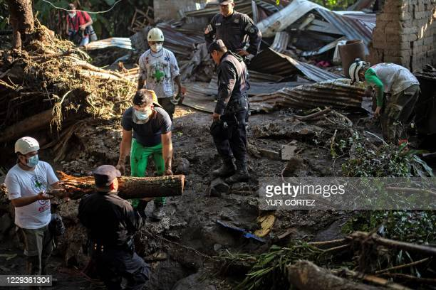 Rescuers of the Green Cross, police and soldiers work to remove rubble while searching for victims of a landslide in Nejapa, El Salvador on October...