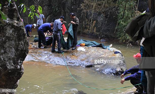Rescuers prepare to carry two bodies of British tourists near a waterfall on the outskirts of the central highland town of Dalat on February 26 2016...