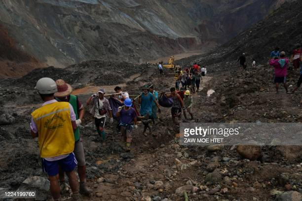 TOPSHOT Rescuers recover bodies near the landslide area in the jade mining site in Hpakant in Kachin state on July 2 2020 The battered bodies of more...