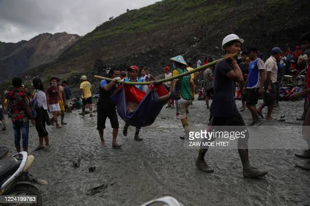 Rescuers recover bodies near the landslide area in the jade mining site in Hpakant in Kachin state on July 2 2020 The battered bodies of more than...