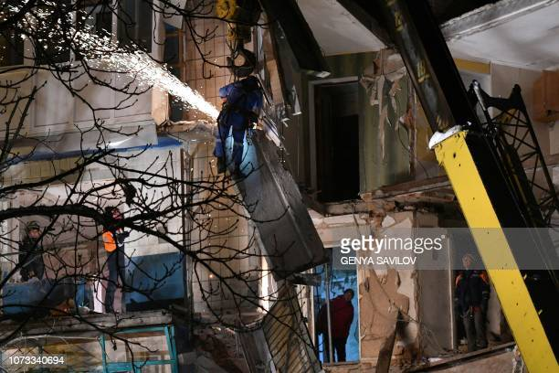 Rescuers remove rubble from a partially destroyed fivestorey building after a gas explosion in Fastiv on December 14 2018 A gas explosion ripped...