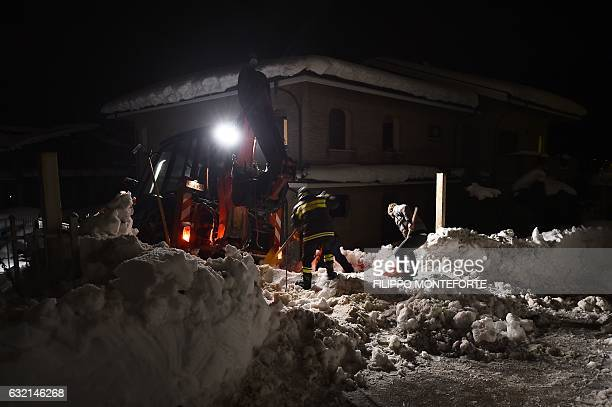 Rescuers remove snow next to a house on a road to the village of Penne after an avalanche engulfed the mountain hotel Rigopiano in Farindola in...