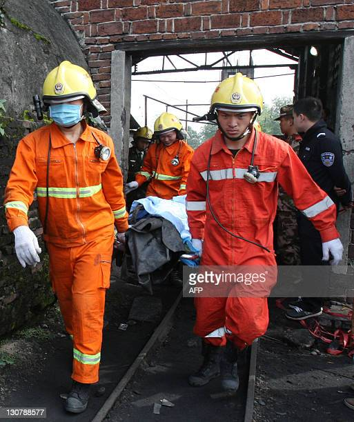 Rescuers remove the body of a miner killed in the explosion at the state-owned Xialiuchong Coal Mine in Hengyang city, central China's Hunan province...