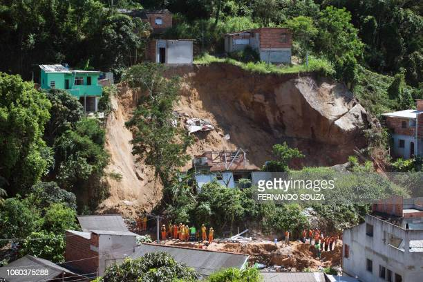 Rescuers residents and workers of Niteroi Cleaning Company inspect the area affected by a landslide that occured on the eve on the Morro da Boa...