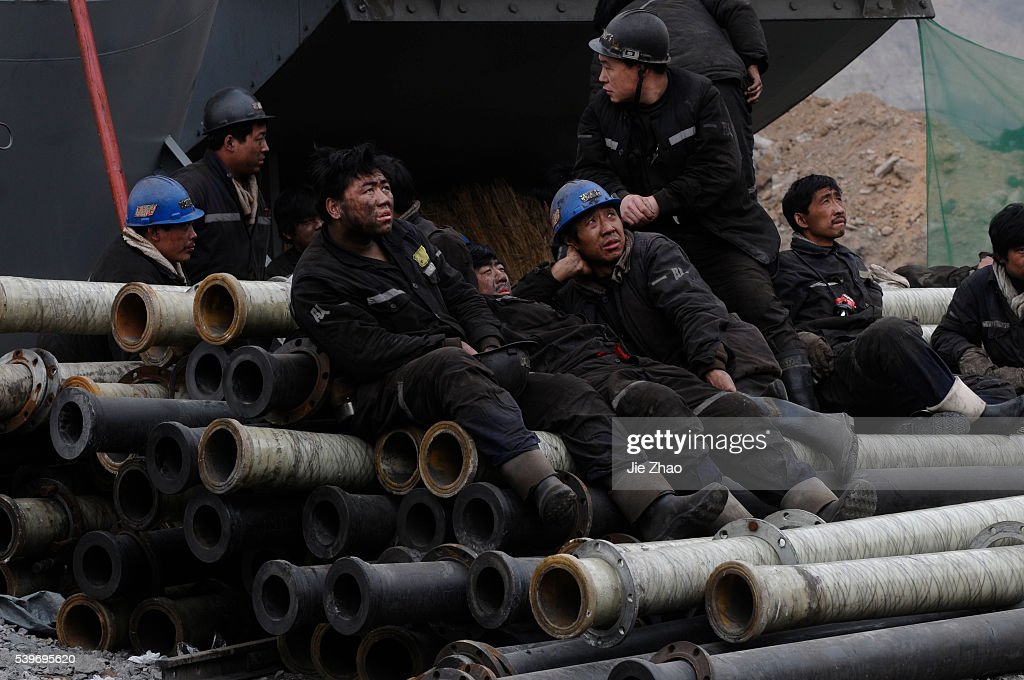 Rescuers rest after a rescuing mission at the site of a flooding accident at the coal mine, sitting astride Xiangning Co : News Photo