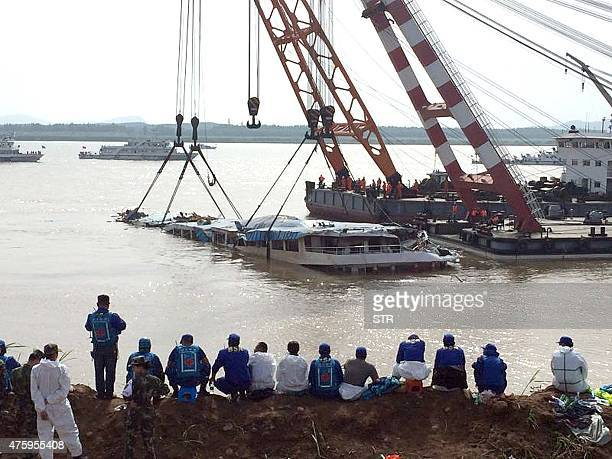 Rescuers rest as they gather to watch the 'Eastern Star' cruise ship on June 4 which had more than 456 people on board when it overturned on June 1...
