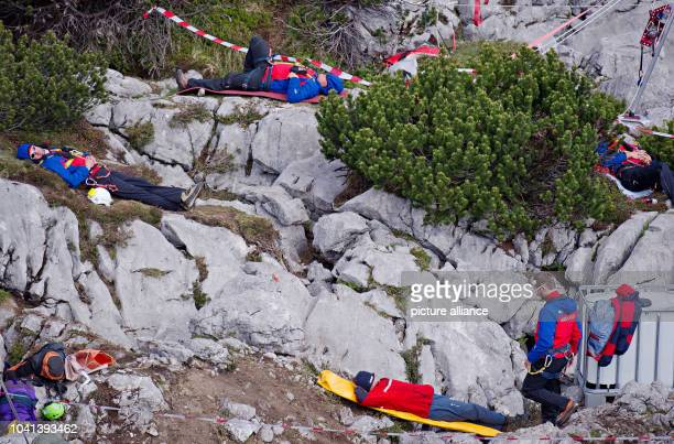 Rescuers rest near the entrance to the Riesending cave at Untersberg mountain near Marktschellenberg Germany 19 June 2014 The seriously injured...