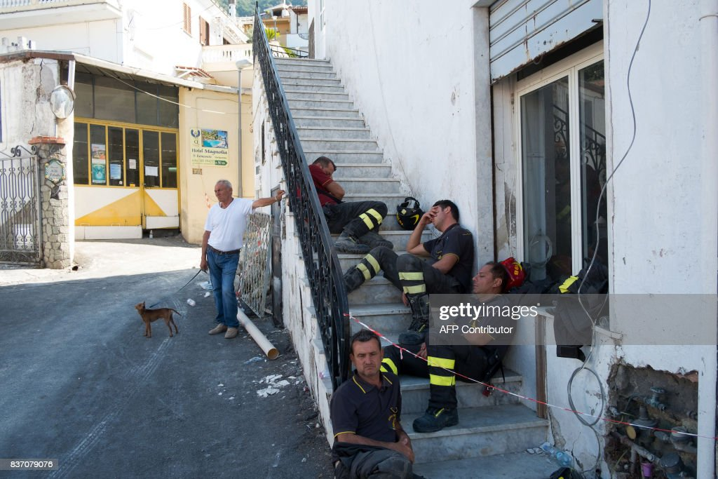 Rescuers rest on steps in Casamicciola Terme, on the Italian island of Ischia, on August 22, 2017, after an earthquake hit the popular Italian tourist island off the coast of Naples, causing buildings to collapse overnight and leaving two dead. Rescuers on the Italian holiday island of Ischia pulled the last trapped child from rubble August 22 after a magnitude-4.0 earthquake toppled buildings and left two people dead. Firefighters dug with their bare hands to reach 11-year old Ciro, the last of three brothers buried in debris when the quake struck. / AFP PHOTO / Eliano IMPERATO