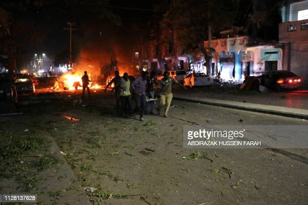Rescuers run as they carry a stretcher in Mogadishu the capital of Somalia on February 28 2019 after a car bomb exploded close to a major hotel...