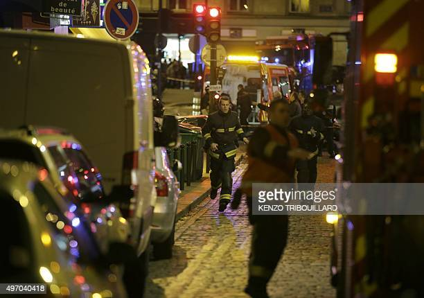Rescuers rush to the scene following an attack in the 10th arrondissement of the French capital Paris on November 13 2015 At least 18 people were...