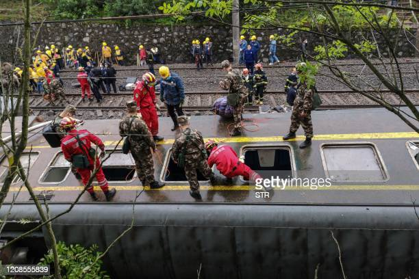 Rescuers search at the site where a train derailed in Chenzhou in China's central Hunan province on March 30, 2020. - A passenger train derailed...
