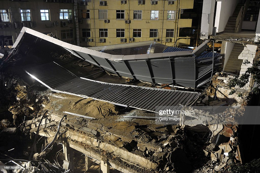 Rescuers search for buried people at the ruins of a four-story building on May 20, 2013 in Fuzhou, China. A four-story building collapsed at around 4 p.m. Monday in Fuzhou. Search and rescue work is ongoing, and the number of casualties is not immediately known.