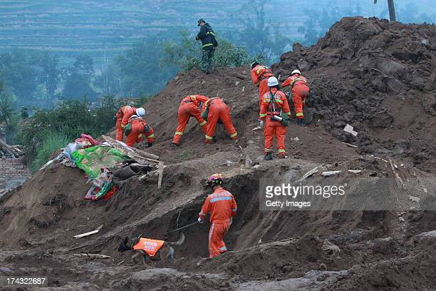 Rescuers search for buried people at the site of a mudslide at Yongguang village on July 23 2013 in Minxian China At least 95 people were killed and...