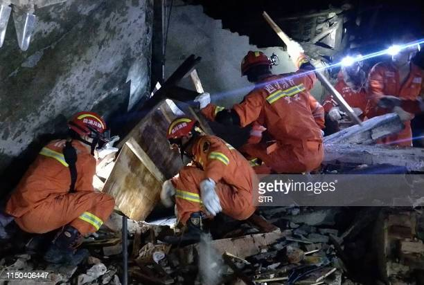 Rescuers search for earthquake survivors in the rubble of a building in Yibin, in China's southwest Sichuan province early on June 18, 2019. - The...