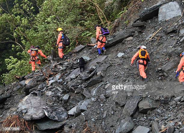 Rescuers search for missing Chinese tourists after their bus convoy was caught in a mudslide on Su Hua road in Ilan county between Hualien and Suao...