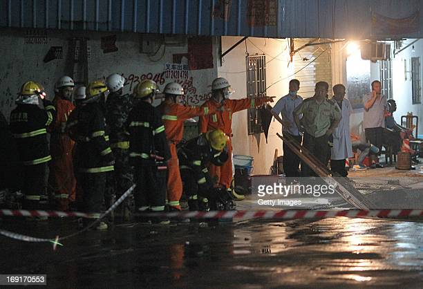 Rescuers search for people buried in a road cave-in accident site on May 21, 2013 in Shenzhen, China. Three people have been confirmed dead and two...