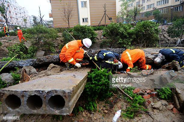 Rescuers search for survivors after an oil pipeline exploded on November 24 2013 in Qingdao China The death toll from the blast that occurred in...