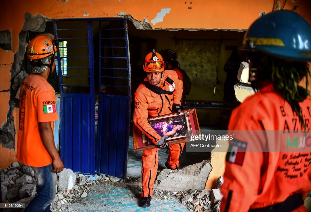 TOPSHOT - Rescuers search for survivors amid houses knocked down or severely damaged by Thursday night's 8.2-magnitude quake, in Juchitan, Oaxaca, Mexico, on September 10, 2017. Rescuers pulled bodies from the rubble and grieving families carried coffins through the streets Saturday after Mexico's biggest earthquake in a century killed 65 people. /