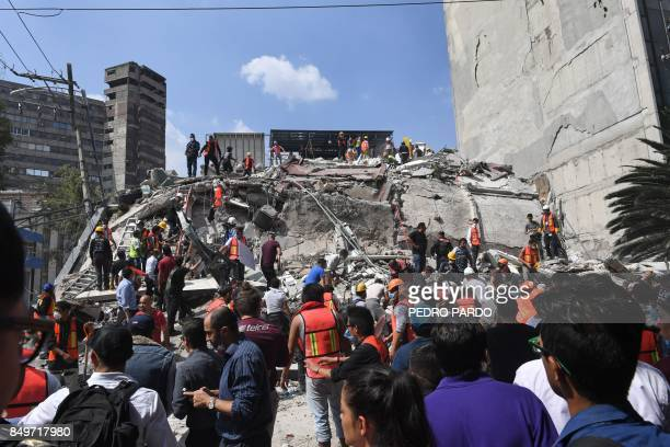 Rescuers search for survivors amid the rubble of a collapsed building after a powerful quake in Mexico City on September 19 2017 A powerful...