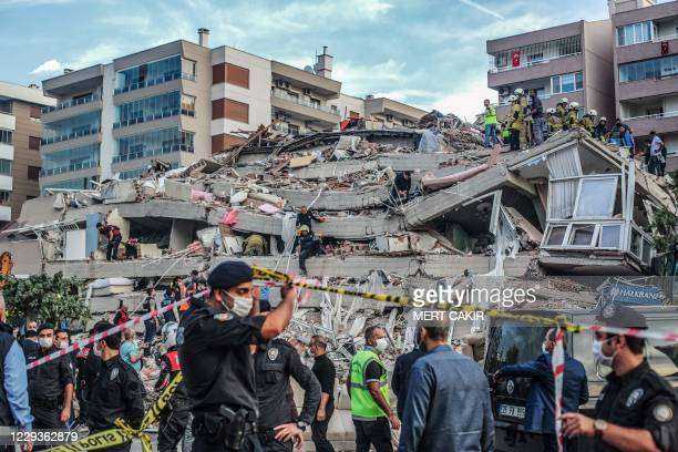 Rescuers search for survivors at a collapsed building after a powerful earthquake struck Turkey's western coast and parts of Greece, in Izmir, on...