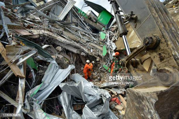 Rescuers search for survivors at the site of a collapsed building in Mamuju on January 16 a day after a 6.2-magnitude earthquake rocked Indonesia's...