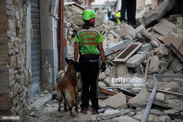 TOPSHOT Rescuers search for victims among the rubble of a house after a strong earthquake hit Amatrice on August 24 2016 Central Italy was struck by...