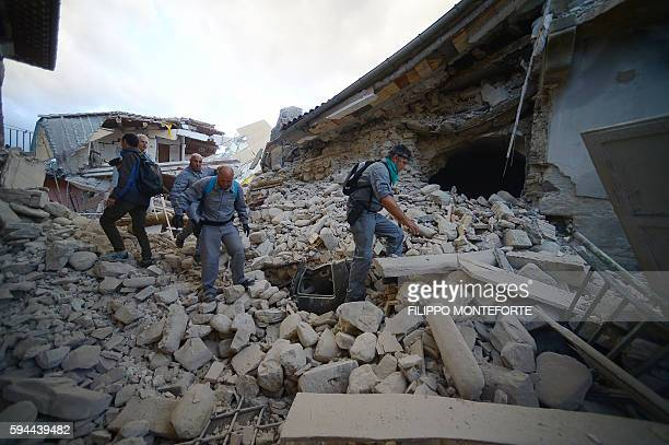 Rescuers search for victims in damaged buildings after a strong earthquake hit Amatrice on August 24, 2016. Central Italy was struck by a powerful,...