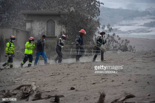 Rescuers search for victims in San Miguel Los Lotes a village in Escuintla Department about 35 km southwest of Guatemala City on June 4 a day after...