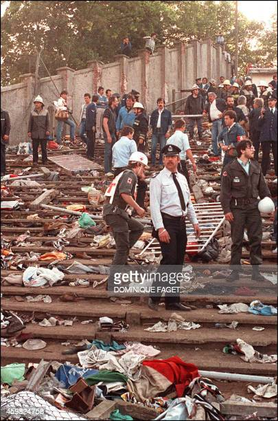 Rescuers search for victims on May 29, 1985 at the scene of riots in Heysel football stadium in Brussels after thirty-nine fans died during violences...
