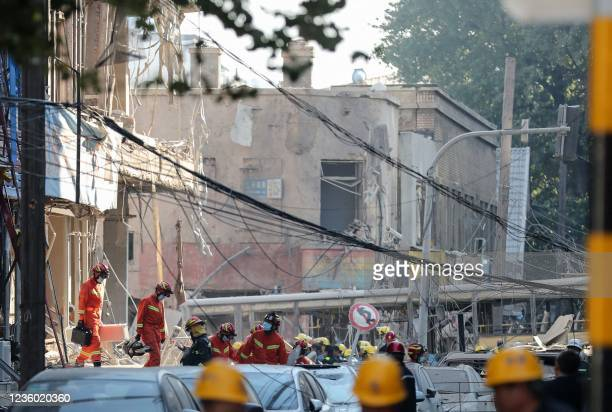 Rescuers search the site of a gas explosion accident at a restaurant after the explosion ripped through a busy street killing at least three and...