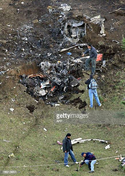 Rescuers see the remains of a helicopter that crashed in Tepango de Rodriguez community in Puebla state Mexico 11 January 2008 The accident occurred...
