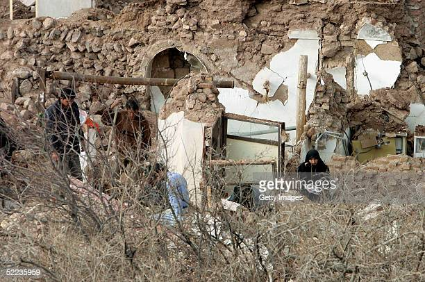 Rescuers sift through the remains of collapsed buildings on February 24 2005 in the ruins of the hillside village of Dahouyeh Iran The earthquake...