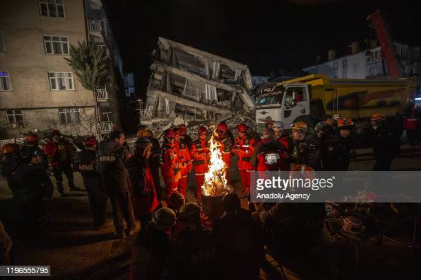 Rescuers stand around a fire keeping themselves warm as search and rescue efforts continue in Sursuru neighborhood after 68magnitude earthquake...