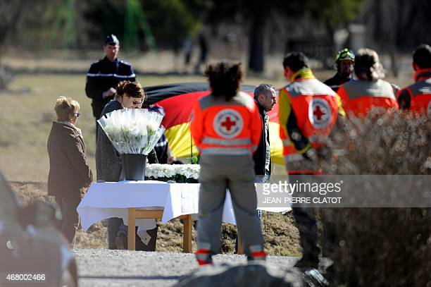 Rescuers stand as relatives of victims pay their respects on March 29 2015 near a commemorative headstone in SeynelesAlpes the closest accessible...