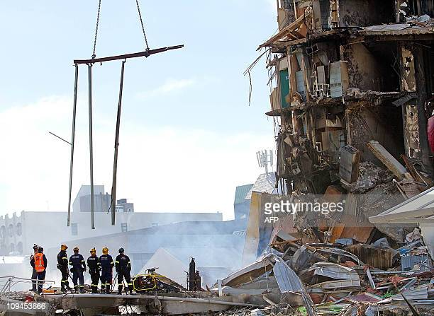Rescuers stand at the smoking ruins of the CTV building where 48 students and staff including scores of Asian students are feared buried in...