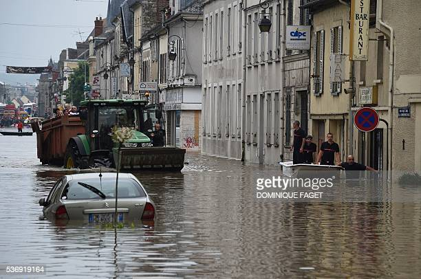 Rescuers stand in a boat as residents ride in the back of a tractor as they are evacuated from a flooded area in Nemours some 80km south of Paris on...